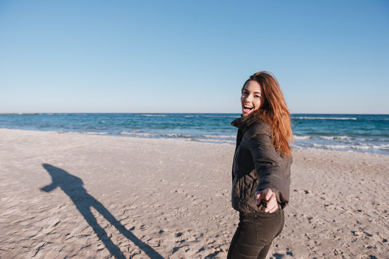Lady happy on a beach looking back with arm reaching out